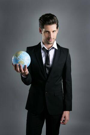 enticement: World globe map sphere in businessman hand over dark gray background