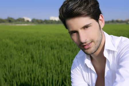 Young man outdoor happy relaxed on green rice field meadow Stock Photo