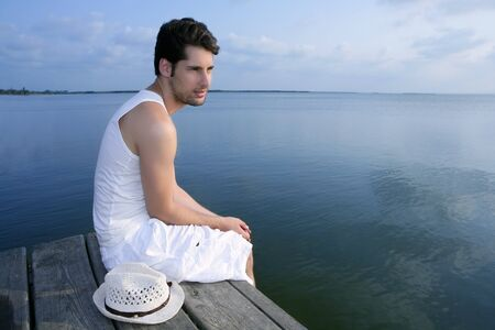 Mediterranean young latin man relaxed on wood pier white hat Stock Photo - 7907604