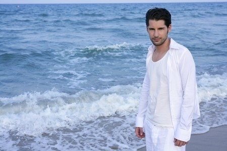 trendy: Latin young man white shirt walking on blue beach outdoor