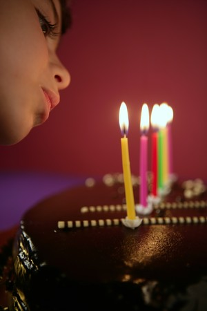 Little girl blowing birthday chocolate cake candles in a row over red background Stock Photo - 7907575