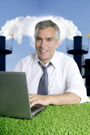 senior businessman working green grass desk computer smog indutrial smoke pollution photo