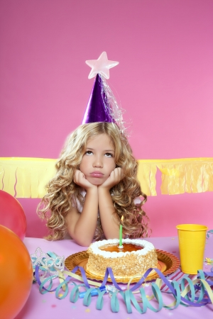 party pastries: bored little blond girl in a birthday party with cake and candle on pink background