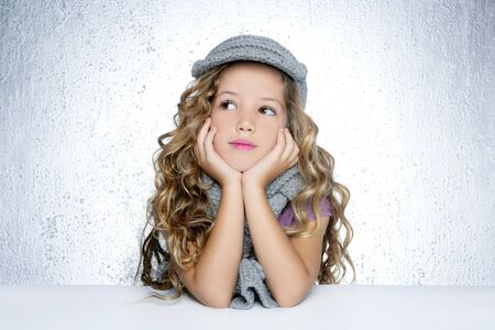 jolie petite fille: laine de PAC hiver foulard le fond gris argent portrait de jeune fille fashion peu Banque d'images