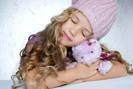 winter fashion cap little girl hug teddy bear smiling silver background photo