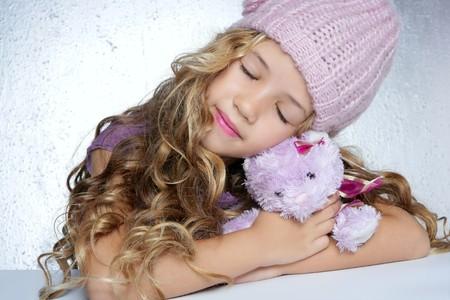 sweet dreams: winter fashion cap little girl hug teddy bear smiling silver background
