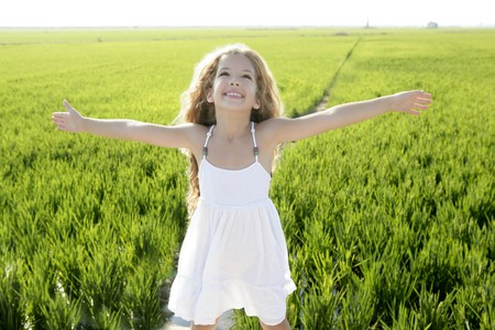 curly hair child: open arms little happy girl green meadow rice field