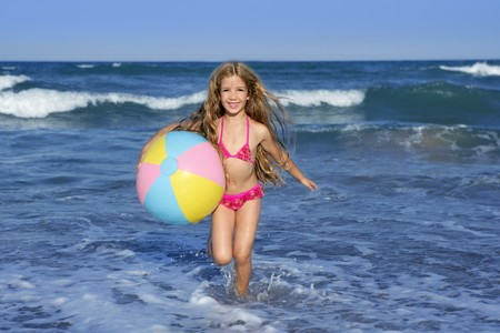 Beach little girl colorful ball vacation playing in blue sea photo