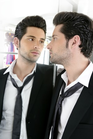 looking in mirror: Handsome narcissistic suit proud young man looking himself in the mirror  Stock Photo