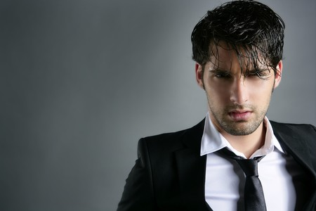 working model: Fashion trendy suit young handsome man messy hairstyle dark portrait on gray