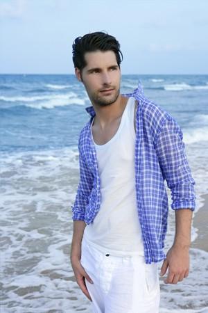 modelos hombres: Relajado mediterr�nea joven Latina en wakling de playa azul de verano  Foto de archivo