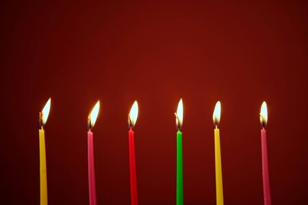 Colorful birthday light candles in a row red background photo