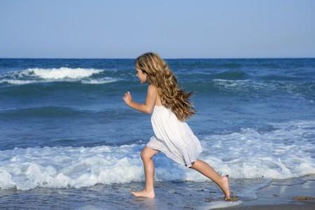 spruzzi acqua: Bambina che correva riva acqua spiaggia spruzzi nel mare blu