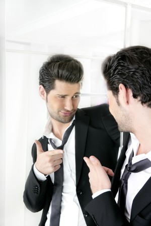 enticement: Handsome suit proud young man humor funny gesturing in a mirror