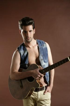 guitarra sexy: Retrato de jugador de guitarra de m�sico de apuesto joven sexy en marr�n