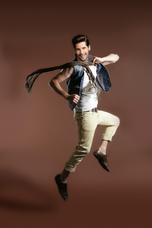 High jumping fly young handsome fashion man on brown background photo