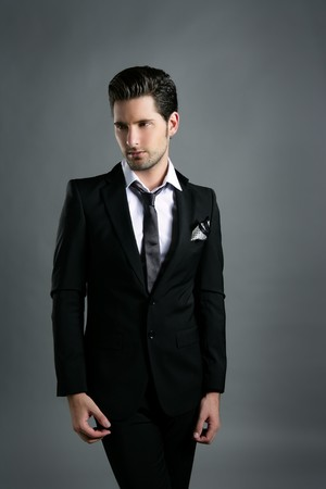 mode: Fashion young businessman black suit casual tie on gray background