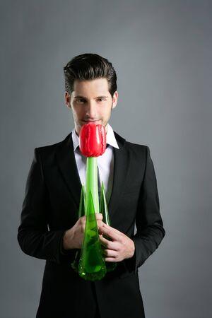 Businessman modern valentine plastic rose flower in hand over gray background photo