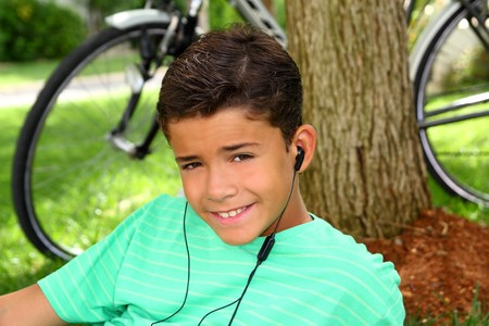 Teen smiling boy hearing music headphones grass sitting tree trunk photo