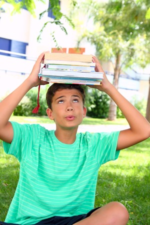 boy teenager student holding head stacked books heavy weight photo