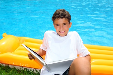 boy student teen vacation homework pool float smiling Stock Photo
