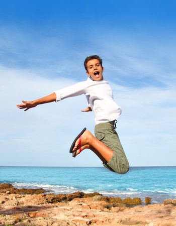 boy teenager high fly jump on beach blue sky summer vacation