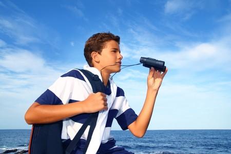boy handsome teenager summer binoculars explorer in blue beach photo