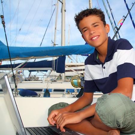 boy teen seat on boat marina laptop computer summer vacation photo