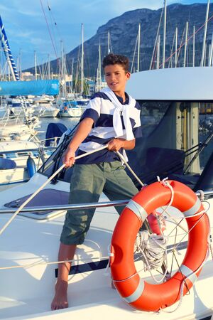 child model: Boy teen sailor mooring boat rope in harbor summer marina standing up
