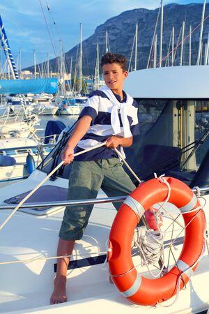 ni�o modelo: Marinero de adolescente chico amarre de cuerda de barco en el puerto de pie de puerto deportivo de verano hasta