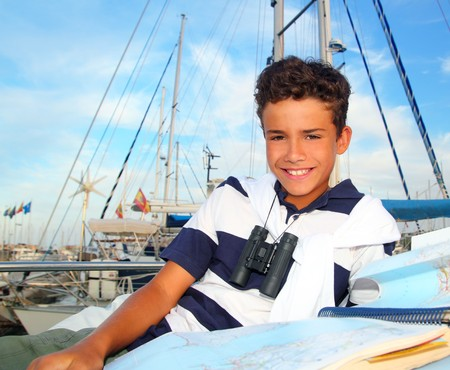 boy teen sailor laying on marina boat chart map smiling in summer vacation Stock Photo - 7992815