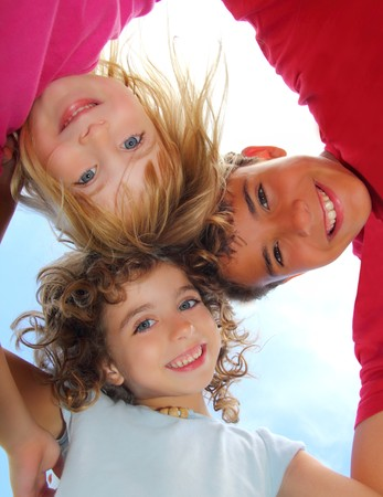 angle views: Below view of happy three children embracing hug each other smiling camera  Stock Photo