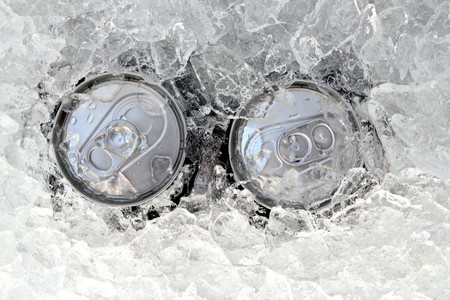 two drink can iced submerged in frost ice closeup photo