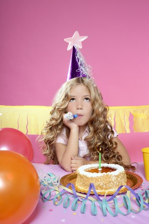 bored little blond girl in a birthday party with cake and candle on pink background photo