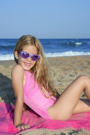 Trendy fashion little summer girl on beach sand tanning with sunglasses Stock Photo - 8051555