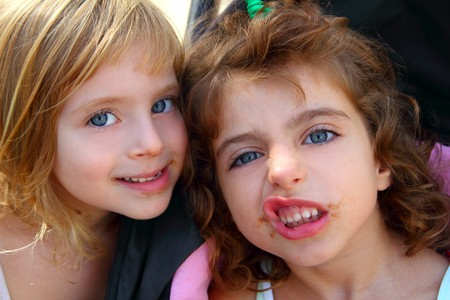 dirty blond: funny two little sister girls funny face gesture dirty mouth Stock Photo