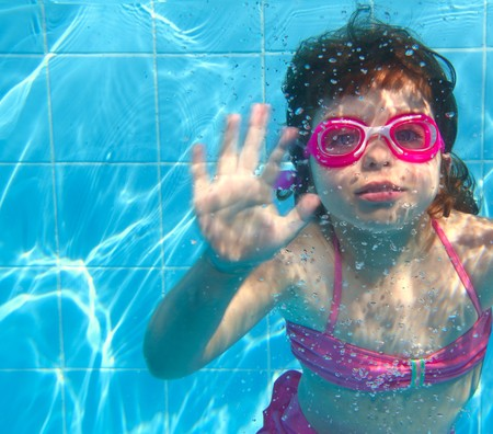 lesson: underwater little girl pink bikini goggles blue swimming pool