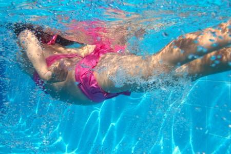 meisje zwemmen: onderwater roze bikini meisje zwemmen in blauwe zwembad
