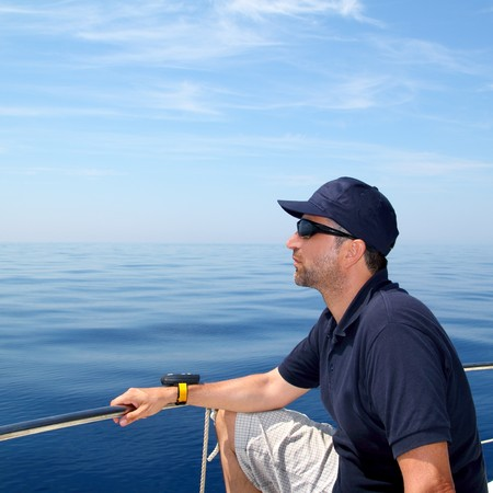 Sailor man sailing boat blue calm ocean water Mediterranean sea photo