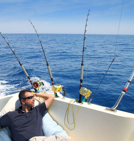 sportfishing: Sailor man fishing resting in boat summer vacation blue sea