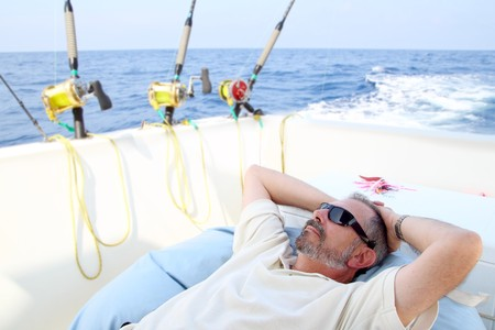 saltwater: Sailor senior fisherman relax on boat fishing deep sea Stock Photo