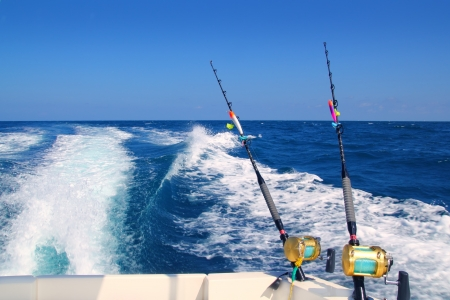 fishing tackle: Trolling fishing boat rod and golden saltwater reels deep blue ocean sea wake Stock Photo