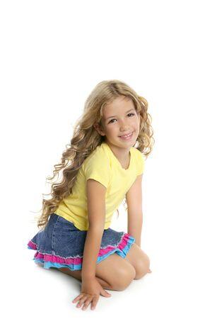 little models: ni�a rubia sonriente retrato en sus rodillas aislados sobre fondo blanco  Foto de archivo