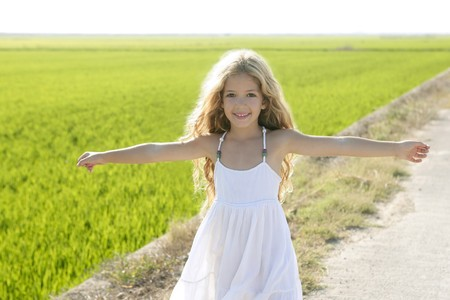 curly hair child: open arms little happy girl green meadow rice field track Stock Photo