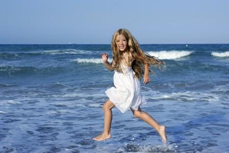 Little girl running beach shore splashing water in blue sea Stock Photo - 8119548