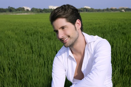 Young man outdoor happy relaxed on green rice field meadow Stock Photo - 8121814
