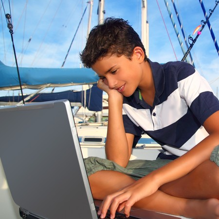 handsome boys: boy teenager seat on boat marina laptop computer summer vacation Stock Photo