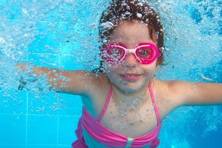 underwater little girl pink bikini goggles blue swimming pool photo