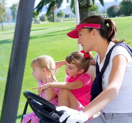 golf course family mother and daughters in buggy green grass field photo