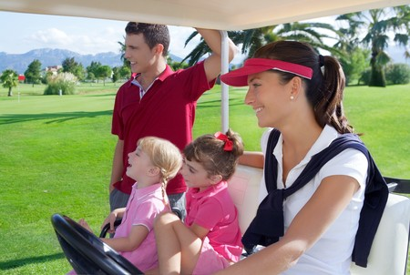 woman golf: golf course family father mother and daughters in buggy green grass field Stock Photo
